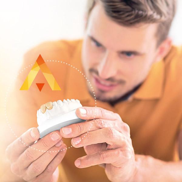 Prothésiste dentaire vérifiant des couronnes antérieures réalisées à partir de céramique pressée VITA
