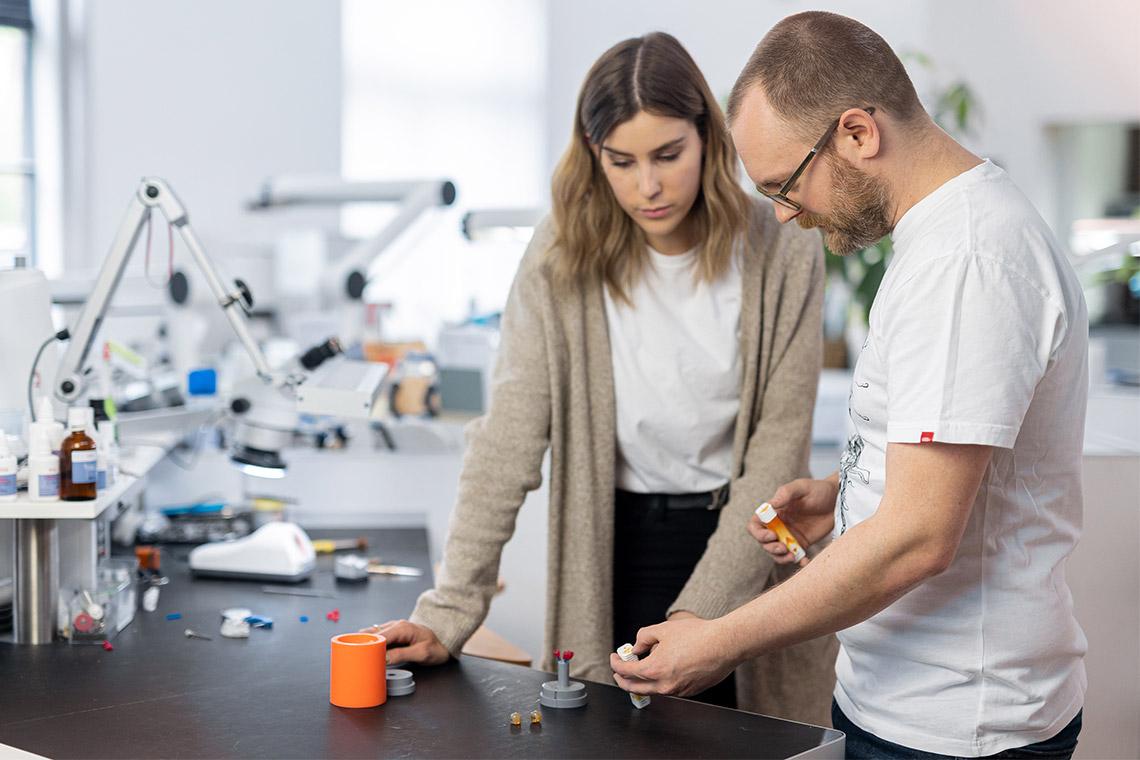 Two dental technicians discussing VITA AMBRIA Press Ceramic