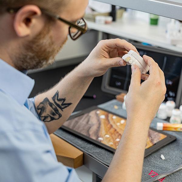 Master Dental Technician Stephan Juckel inspects a crown made of VITA Press Ceramic
