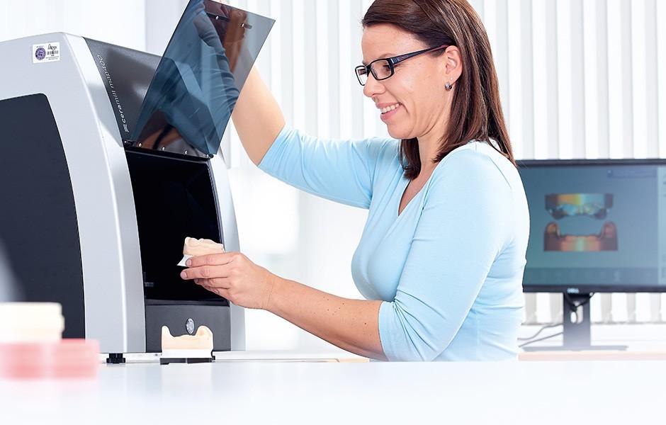 Eine Zahntechnikerin holt ein Gipsmodell aus einem Scanner