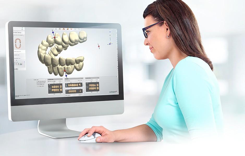 Die Zahntechnikerin erstellt die Prothese im CAD System, auf dem Bildschirm wird die Position eines Zahns angepasst