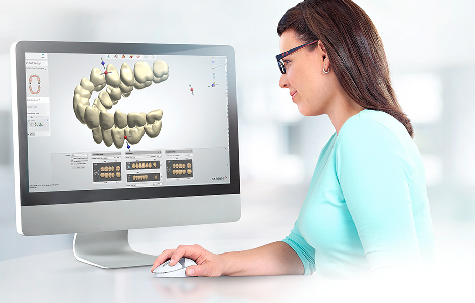 A dental technician works with a CAD program and adjusts the position of a tooth.