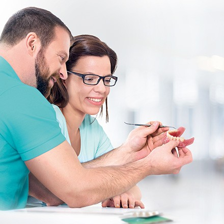 """Link to the report """"Digital denture without aesthetic compromise"""", dental technician in the background"""