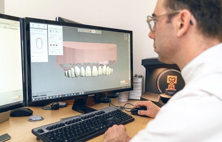 Dental technician Okke Kamps checks the virtual set-up of the teeth on the computer.