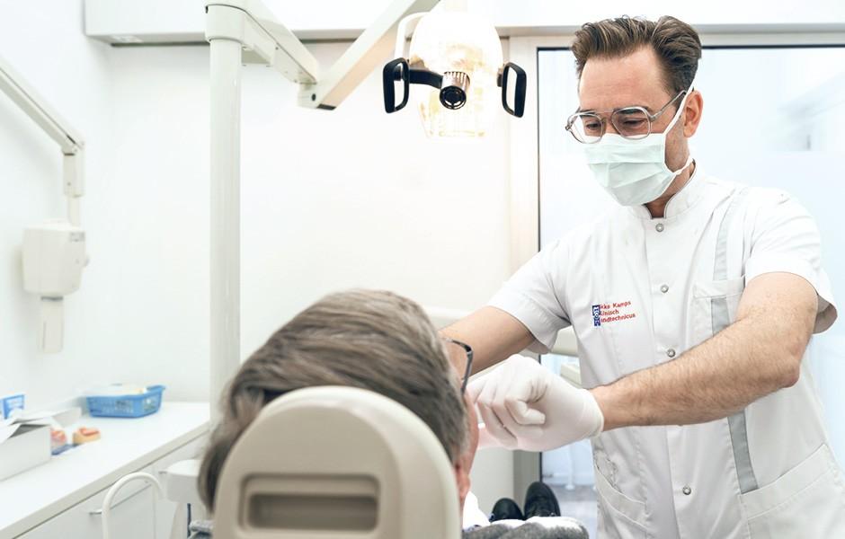 El protésico dental Okke Kamps y un paciente durante la prueba en boca de una prótesis.