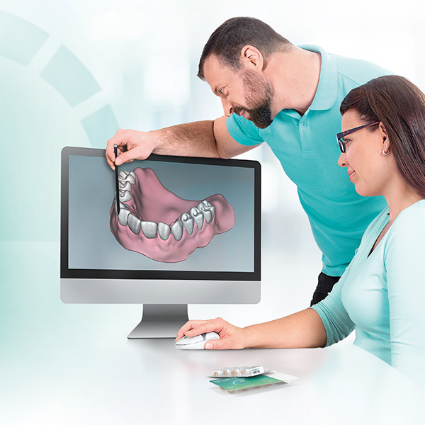 Two dental technicians working on the digital design of a denture